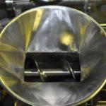 Hopper feeding into screw conveyor