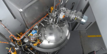Technical cubicle: The top view of 1 000 l processing vessel showing connections, 2nd manway (maintenance) and motor with gearbox